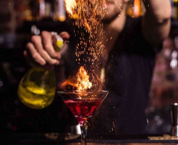 The bartender makes a cocktail of fire.